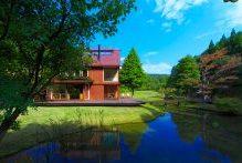 森の中に建つ池のほとりの赤い三角屋根のカフェ