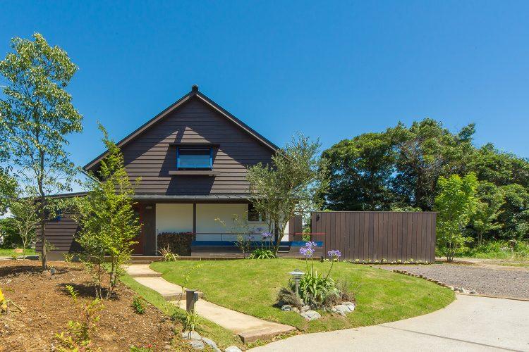 三角屋根の緑に包まれたシンケンスタイルの木の家